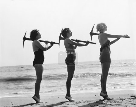 Three women posing with a pick ax on the beach