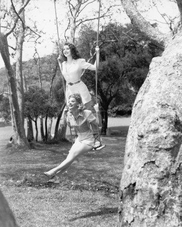 Photo pour Deux femmes, assis ou debout sur une balançoire - image libre de droit