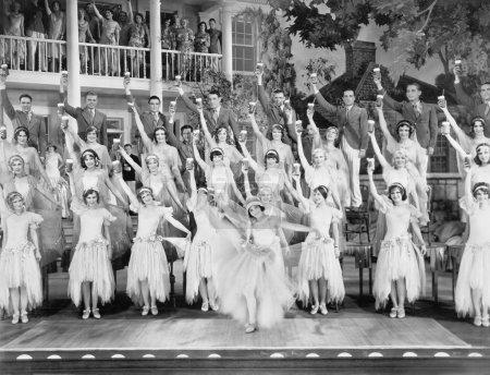 Photo pour Groupe de danseurs debout sur une scène avec les bras en l'air et un verre dans les mains - image libre de droit