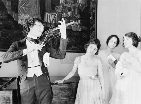 Three young women looking with adoration at a violin player
