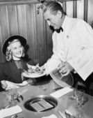 Waiter serving food to a woman at a restaurant