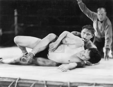 Two men wrestling with a referee in the background