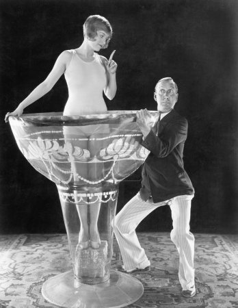 Woman standing in an oversized glass with a man tr...