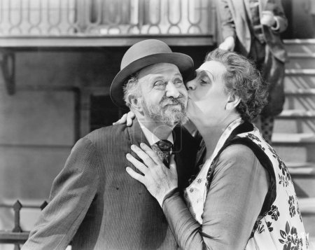 Woman kissing a man on his cheek