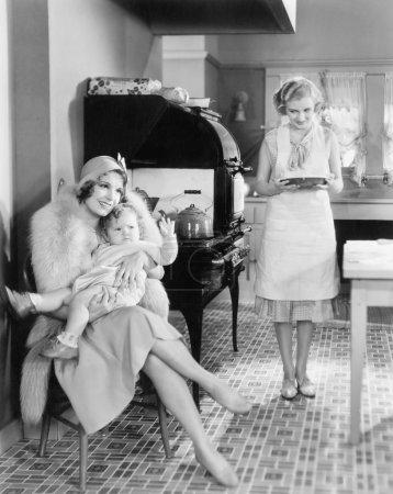 Foto de Elegante mujer sentada con su bebé en la cocina mientras un amigo va a traer un pastel - Imagen libre de derechos