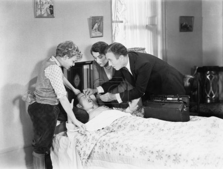 Doctor with the help of a mother and brother trying to give a sick child medicine