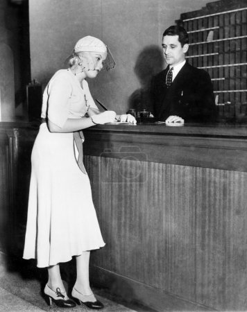 Woman standing at the counter of a hotel where she is checking in