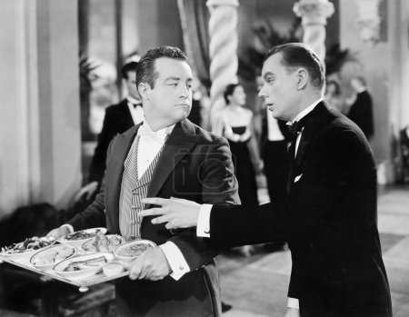 A waiter and patron at a gala event