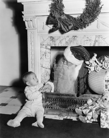 Santa Claus with a little boy in front of a fireplace