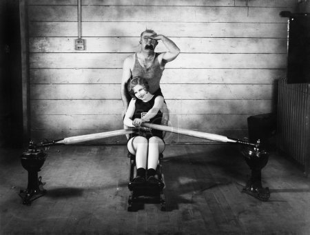 Woman sitting on a rowing machine with a man behind her