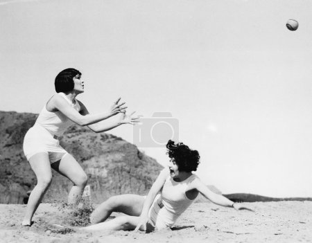 Two women playing with a ball at the beach