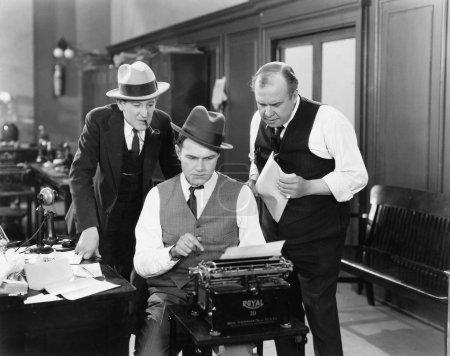 Photo pour Trois hommes dans un bureau penchés sur une machine à écrire - image libre de droit