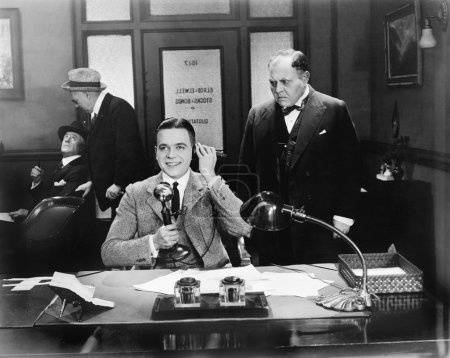 Men at an office one on the telephone