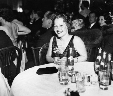 Photo pour Femme assise à une table dans un club - image libre de droit