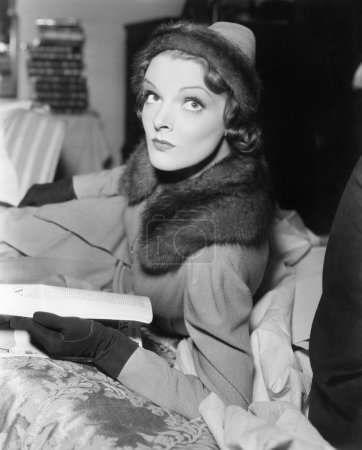 Woman in coat and hat reading a magazine