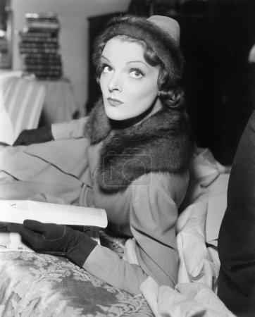 Mujer con abrigo y sombrero leyendo una revista