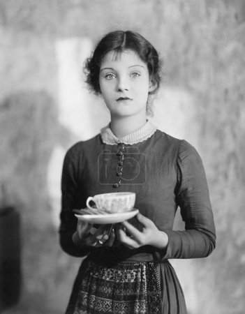 Woman standing with a cup of tea resting on her fingers