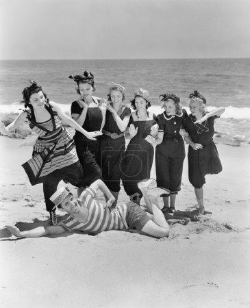 Photo pour Jeune homme avec un groupe de jeunes femmes à la plage - image libre de droit