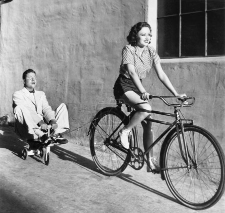 Woman on a bicycle pulling a grown man on a toy tr...