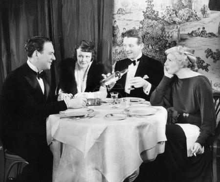 Photo pour Amis assis ensemble à une table de dîner - image libre de droit