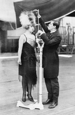 Photo pour Homme prenant une mesure d'une femme avec un chapeau surdimensionné - image libre de droit
