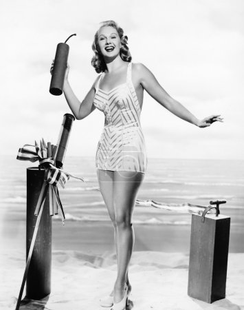 Woman in a bathing suit at the beach holding an ov...