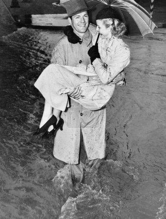 Young man carrying a woman through a rainstorm
