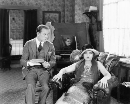 Man and woman sitting in a living room reading a letter and looking surprised