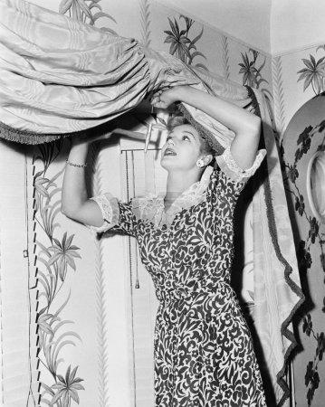Woman hanging a valance