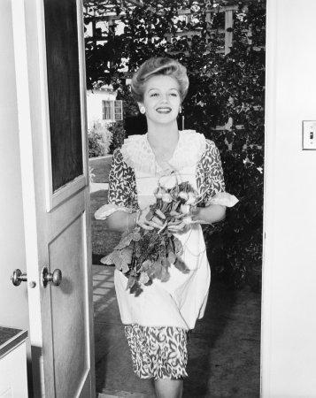 Photo pour Femme marchant à travers une porte avec des fleurs dans ses mains - image libre de droit