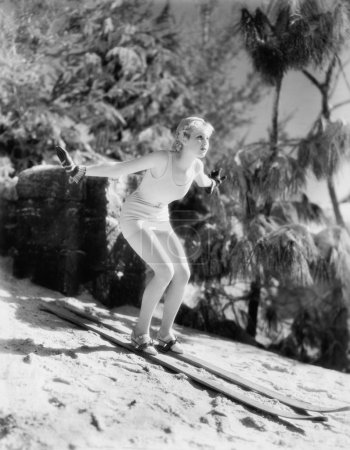 Woman In a bathing suit skiing down a hill