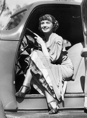 Woman sitting in a car behind the steering wheel