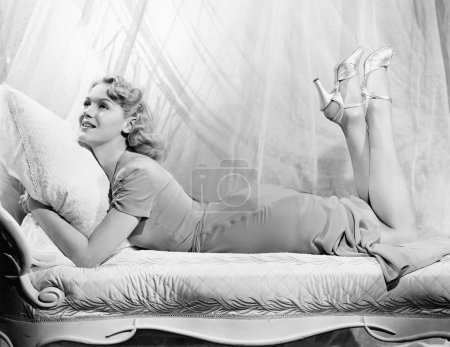 Woman lying on a chaise lounge with her legs up