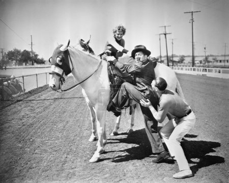 Young couple trying to help a man get onto his horse