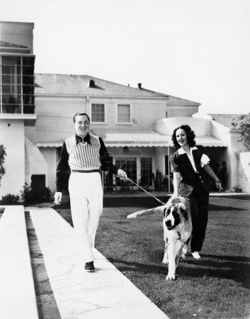 Couple walking their St. Bernard outside their home