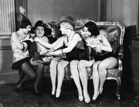 Man dressed Napoleon surrounded by young women