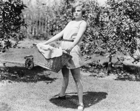Photo pour Jeune femme portant un panier de linge - image libre de droit