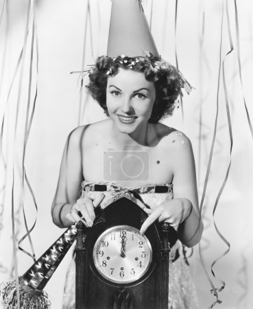 Woman pointing at the clock at midnight