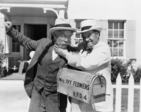 Two mature men fighting near a mail box in front of a house