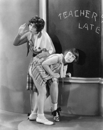 Teacher spanking a girl in a classroom