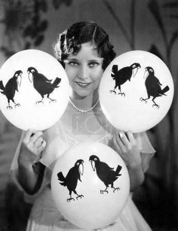 Photo pour Portrait d'une jeune femme équilibrant des ballons sur ses mains et ses genoux - image libre de droit