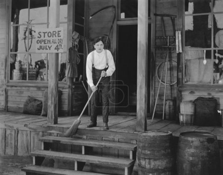 Man sweeping steps in front of store