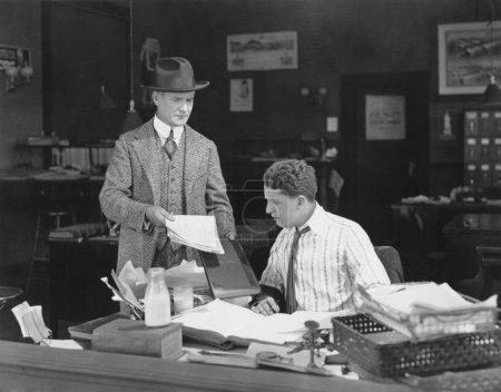 Photo pour Homme avec attitude montrant des papiers à un employé de bureau - image libre de droit