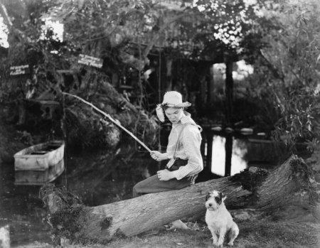 Young man fishing with his dog