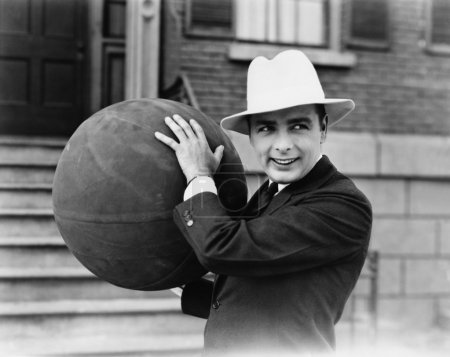 Man in hat holding large ball