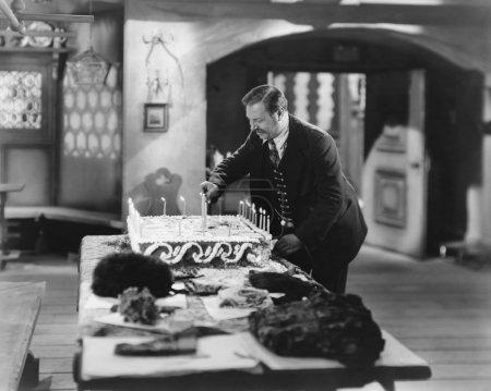 Photo pour Homme allumant des bougies sur gâteau - image libre de droit