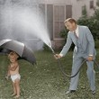 Toddler and dad playing with hose in yard...