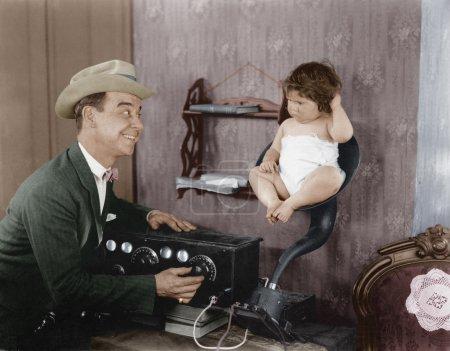 Photo pour Père avec bébé dans haut-parleur corne de vieille radio - image libre de droit