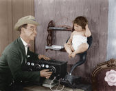 Father with baby in speaker horn of old radio