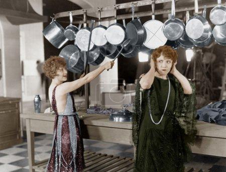 Photo pour Femme dans la cuisine battant sur des casseroles et des casseroles - image libre de droit
